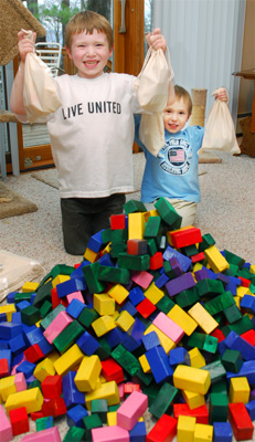 Ryan & Collin preparing Easy Builder building block sets for donation to Toys for Tots and SOS Shelter