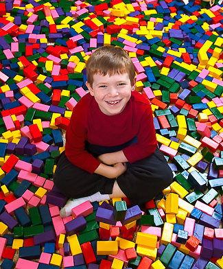 Ryan Steadman sitting surrounded by building blocks!